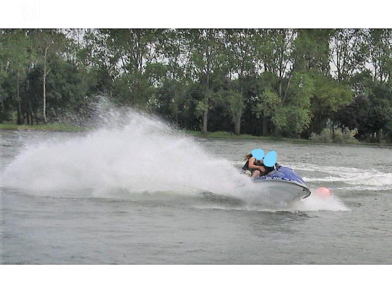 photo dun jet ski sur un lac avec deux personnes.
